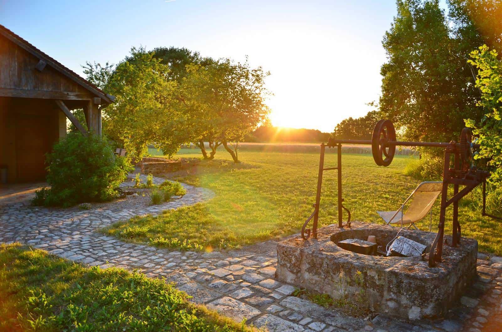 Vieux puits à l'entrée de la pelouse au coucher de soleil - gîte rural de Haute Forêt en Vallée du Loir